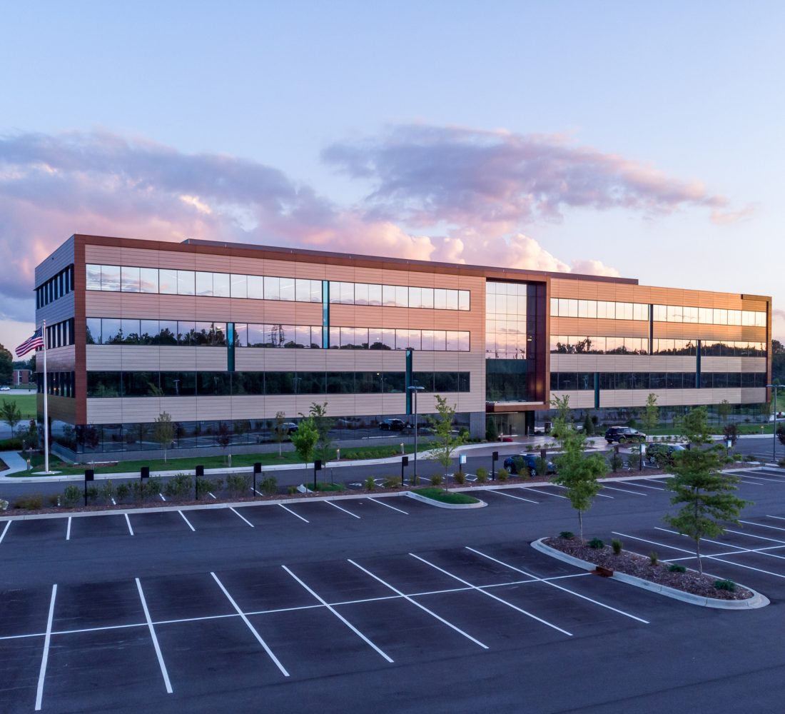 Evening shot of office building exterior with large parking lot